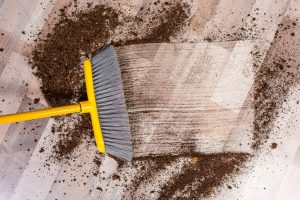 Close-up top view of broom sweeping floor with soil