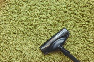 The head of a vacuum cleaner brush on the green carpet, the top view.